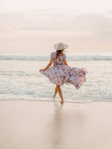 Attraktive Frau im Sommerkleid am Strand des Ozeans bei Sonnenuntergang. – Foto