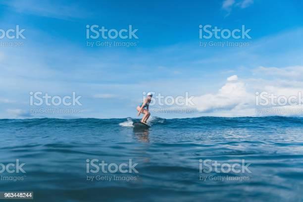 Atrakcyjna Kobieta W Kostiumie Kąpielowym Surfing W Oceanie - zdjęcia stockowe i więcej obrazów Bali