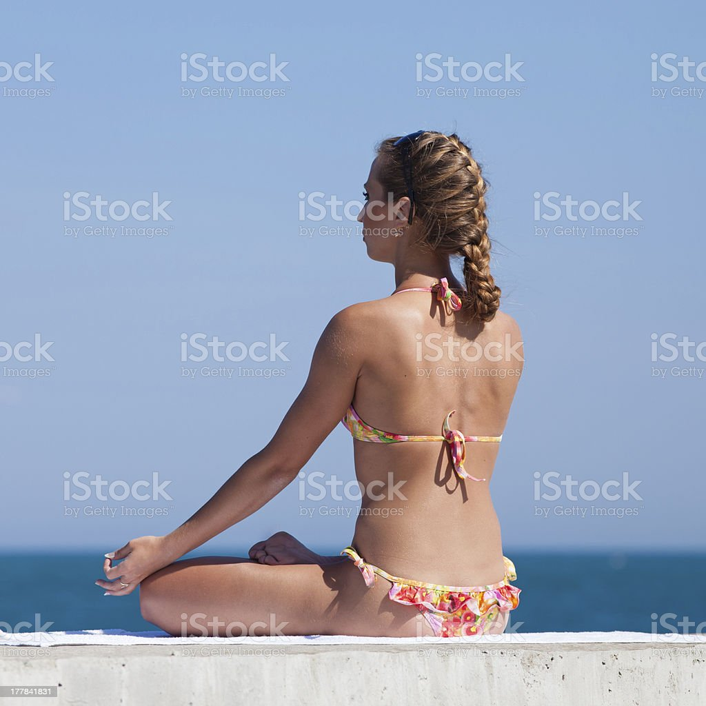Attractive woman in swimwear doing yoga at the sea royalty-free stock photo