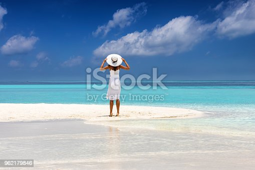 Attractive woman in white dress stands on a tropical beach with turquoise waters and enjoys her summer holiday