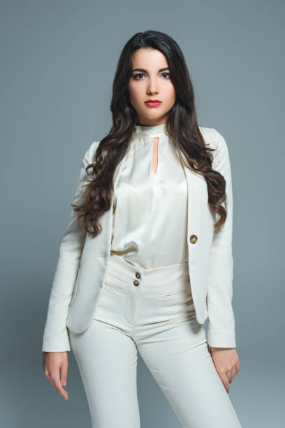 attractive woman in white elegant suit, isolated on grey - white suit stock photos and pictures