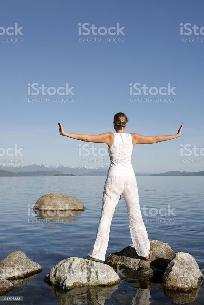 Attractive woman in white meditating by still water royalty-free stock photo