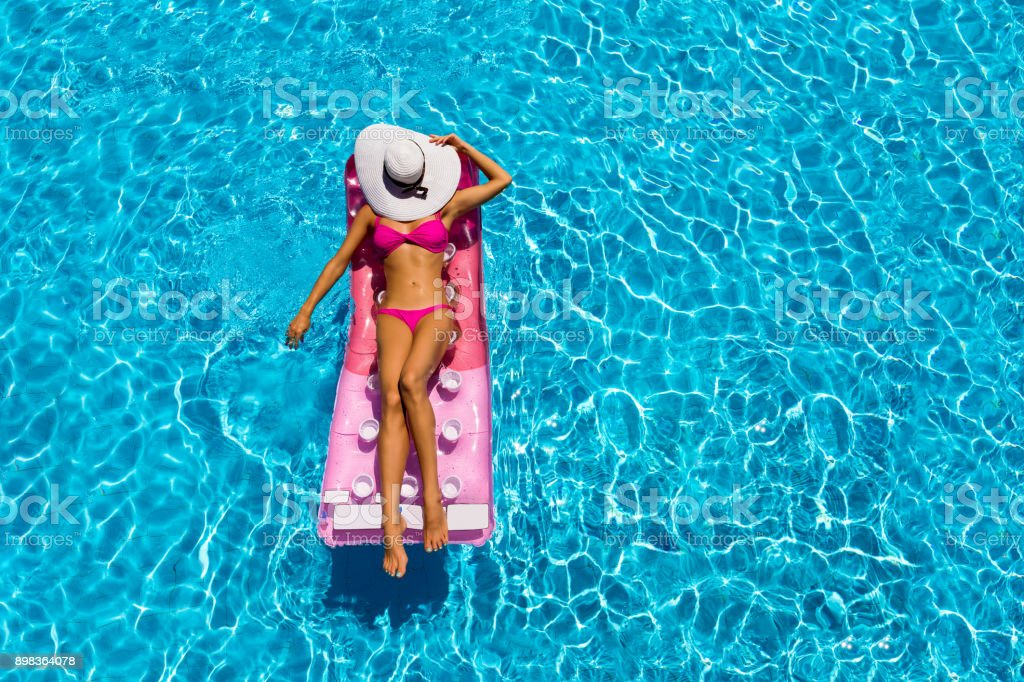 Attractive woman is relaxing on a floating mattress in a pool stock photo