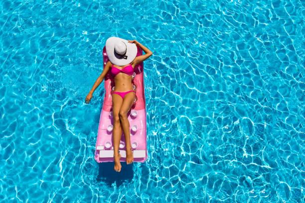 mulher atraente é relaxante em um colchão flutuante em uma piscina - biquíni - fotografias e filmes do acervo
