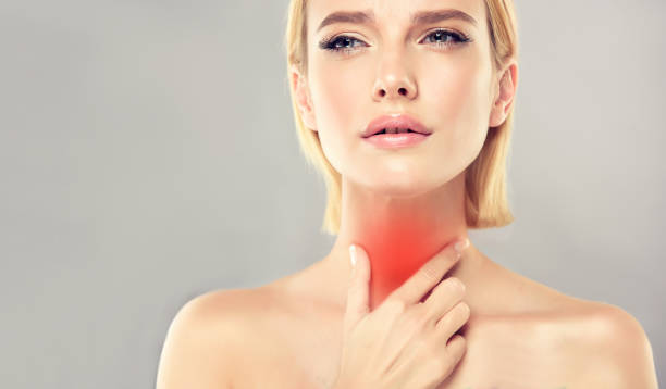 Attractive woman is touching the neck with expression of pain on the face. Sore throat and any type of inflammation. Young, attractive woman is touching the neck with expression of sharp pain on the face. Symbolic image of sore throat, any type of inflammation, endocrinology problems, thyroid gland diseases. endocrine system stock pictures, royalty-free photos & images
