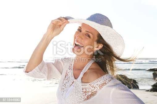 istock Attractive woman laughing with hat at the beach 511544590