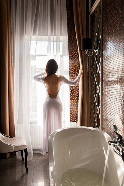 Attractive woman looking at window and preparing to take bath stock photo