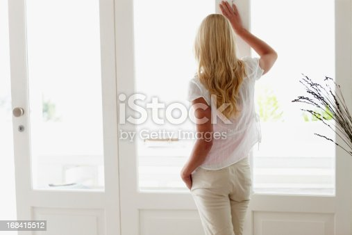 Rear view of attractive woman standing and looking out through window