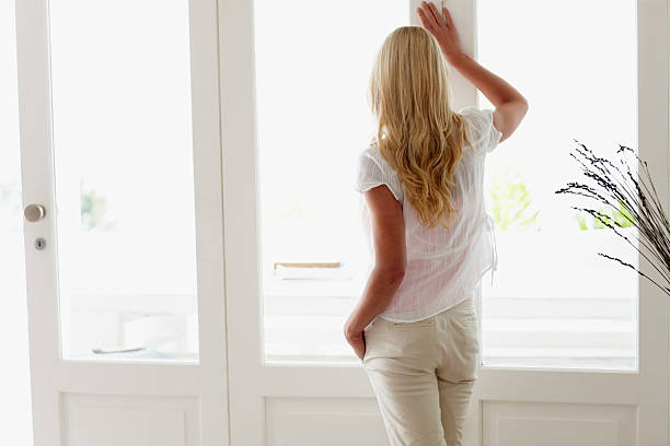 Attractive woman looking out through window stock photo