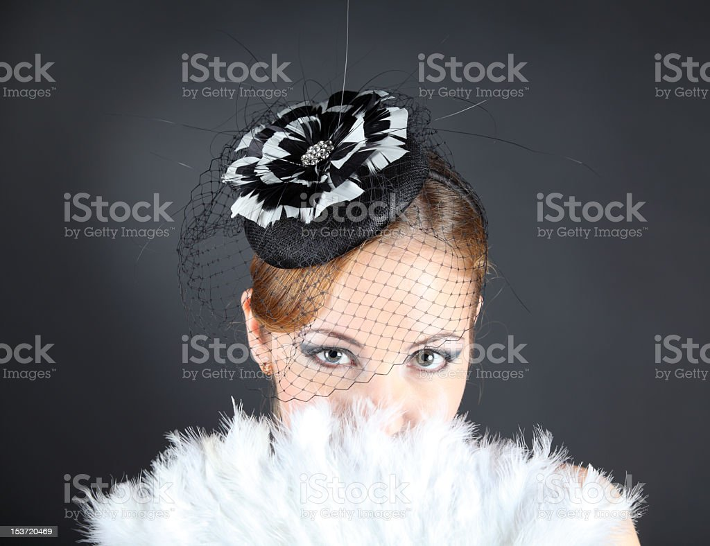 Attractive woman looking through white fan and black veil stock photo