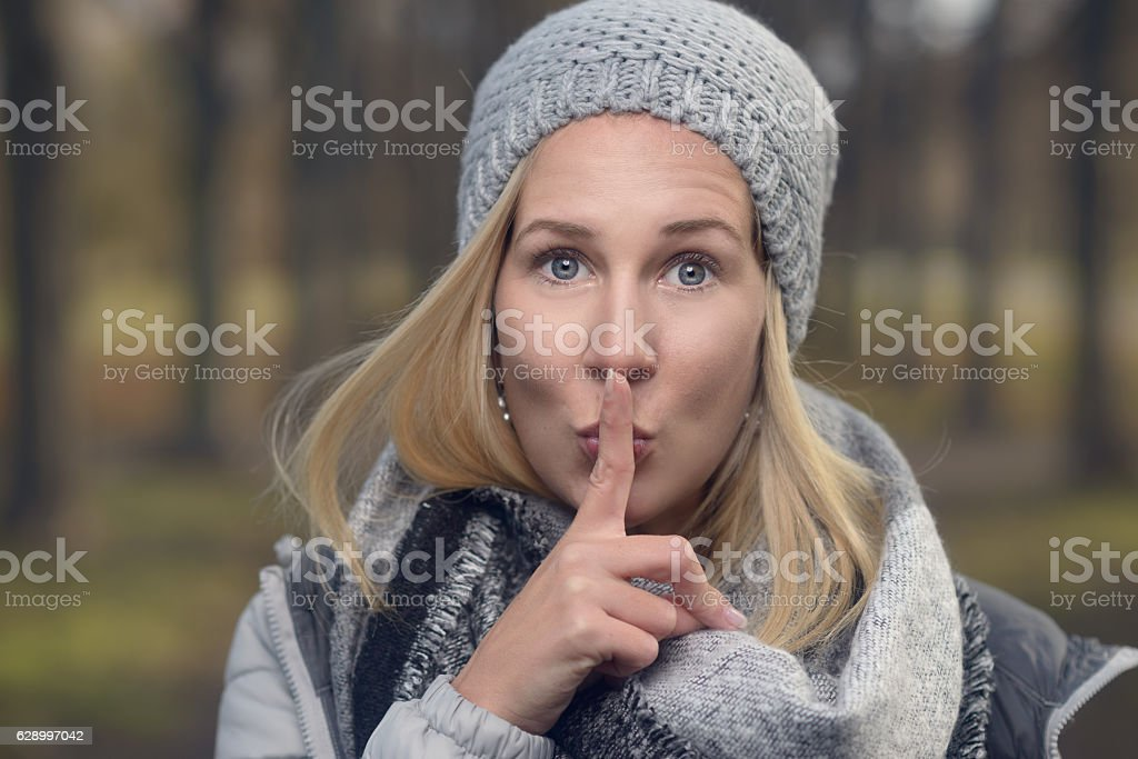 Attractive woman making a shushing gesture stock photo