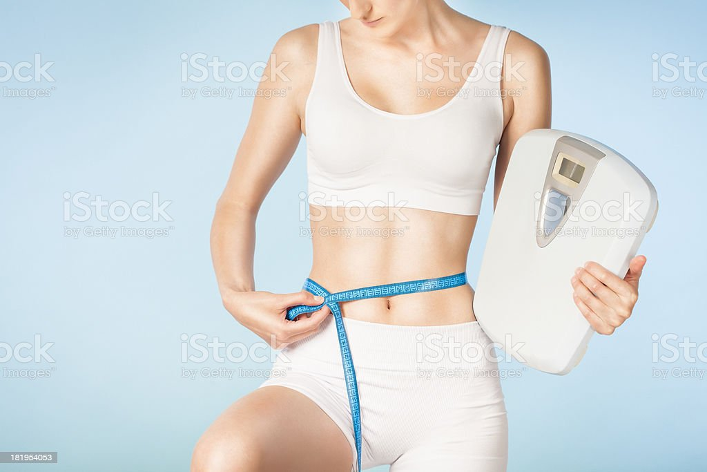 Attractive woman measuring her waist royalty-free stock photo