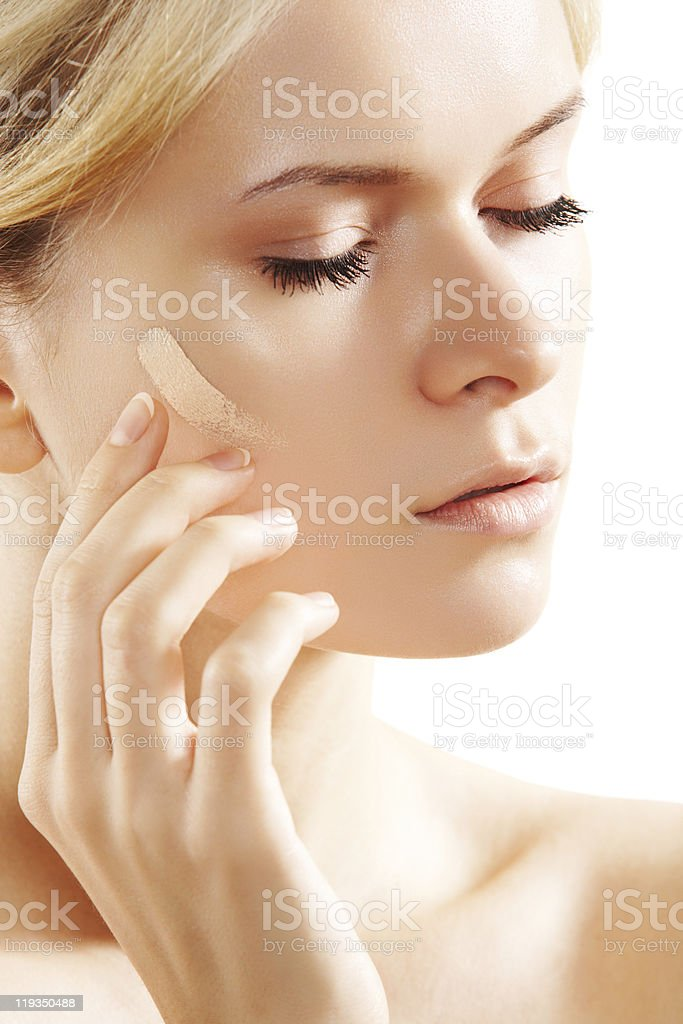 Attractive woman model applying make-up skin foundation stock photo