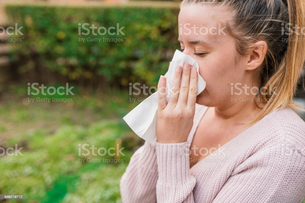 Attractive woman outdoor with tissue having allergy. Woman blowing...