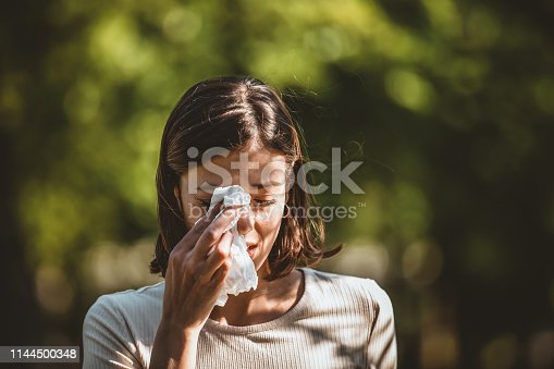 Woman Blowing Her Nose With Handkerchief In Public Parkf. Sick Young Woman With Seasonal Influenza Blowing Her Nose On A Tissue. Seasonal Virus Infection. Chronic Disease Control, Allergy Induced Asthma Remedy And Chronic Pulmonary Disease Concept.