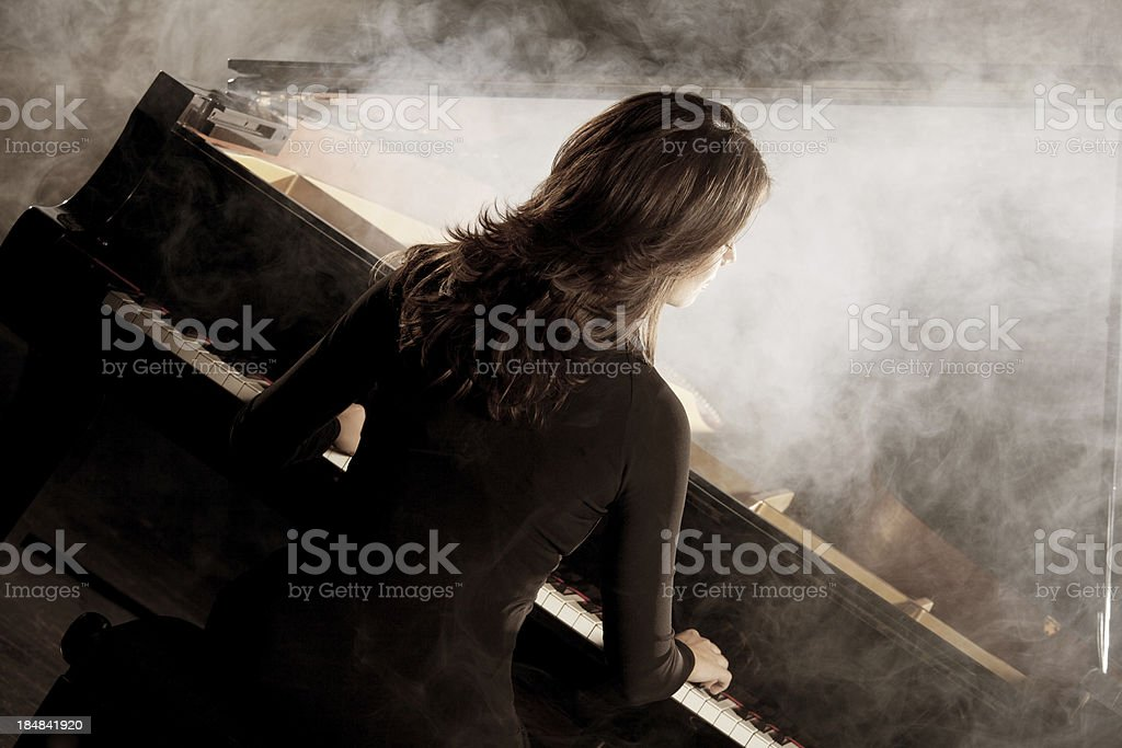 Attractive woman playing piano in the dark theatre stock photo