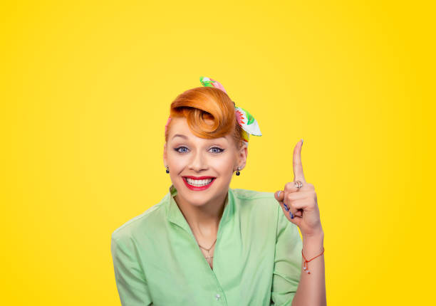 attractive woman pointing finger up has a brilliant idea - pin up girl stock pictures, royalty-free photos & images