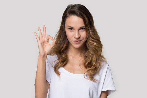 istock Attractive woman posing in studio showing ok sign 1147400453