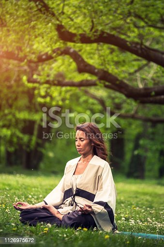 istock attractive woman practicing yoga in nature 1126975672