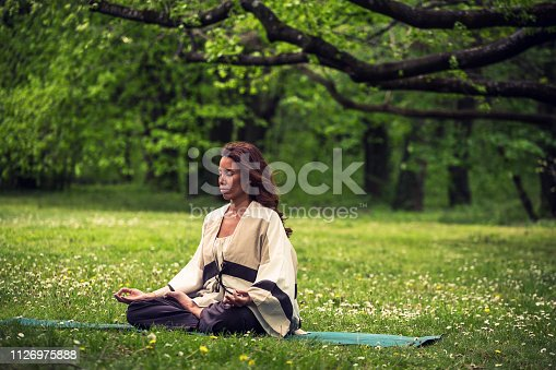 istock attractive woman practicing yoga in nature 1126975888