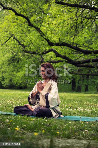 istock attractive woman practicing yoga in nature 1126977441