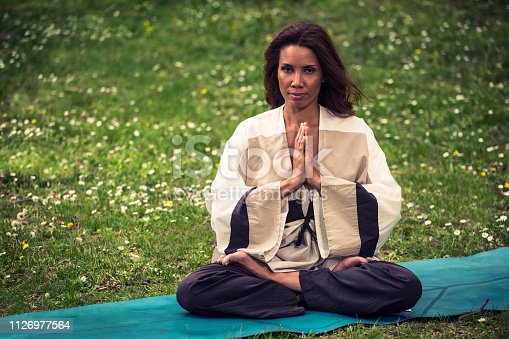 istock attractive woman practicing yoga in nature 1126977564