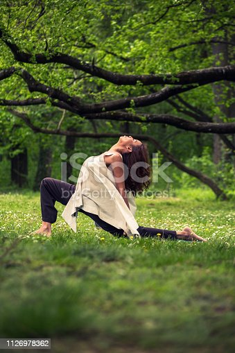 istock attractive woman practicing yoga in nature 1126978362