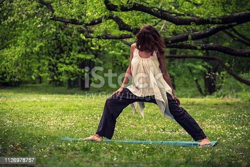istock attractive woman practicing yoga in nature 1126978757
