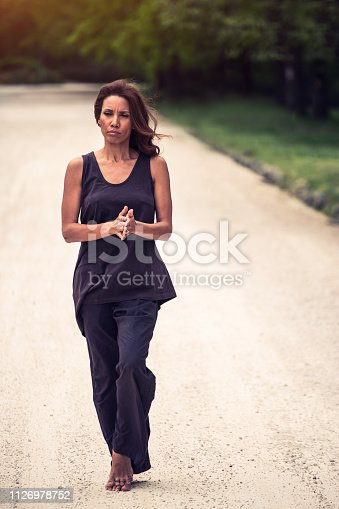 istock attractive woman practicing yoga in park 1126978752