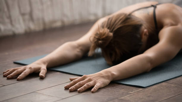 attractive woman practicing yoga, relaxing after training, lying face down - yin yang symbol stock pictures, royalty-free photos & images