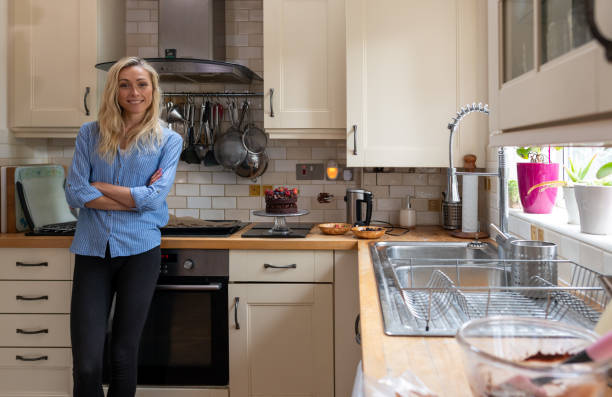 Attractive woman presents a home-made cake in the kitchen stock photo