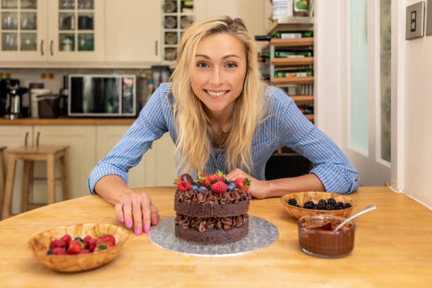Attractive woman presents a home-made cake stock photo