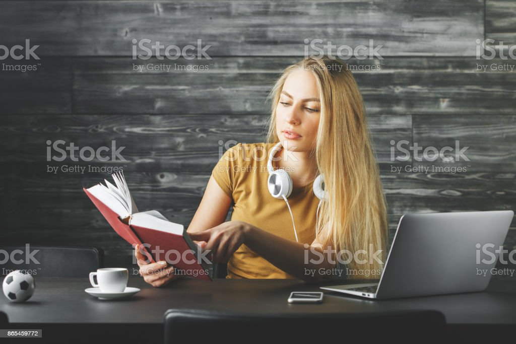 Attractive woman reading book at desk stock photo