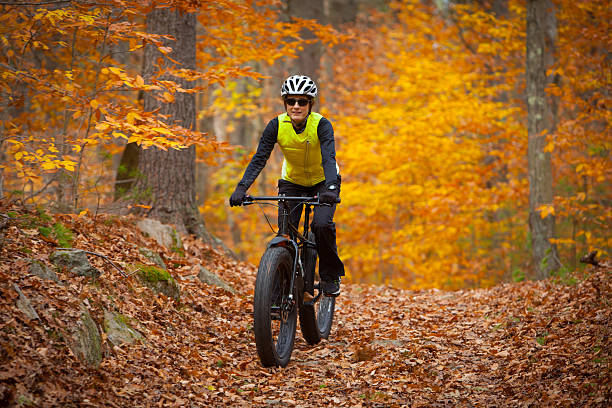 Attractive woman riding a fatbike on leaf covered trail stock photo