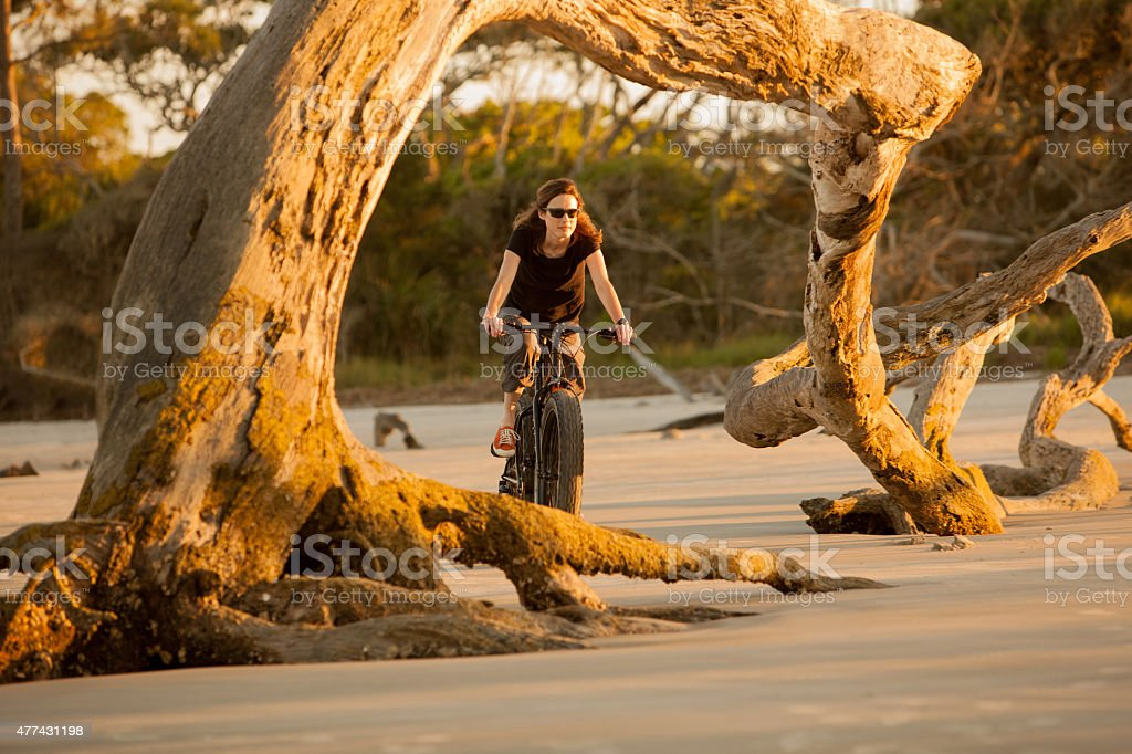 Attractive woman riding her fatbike on the beach. stock photo