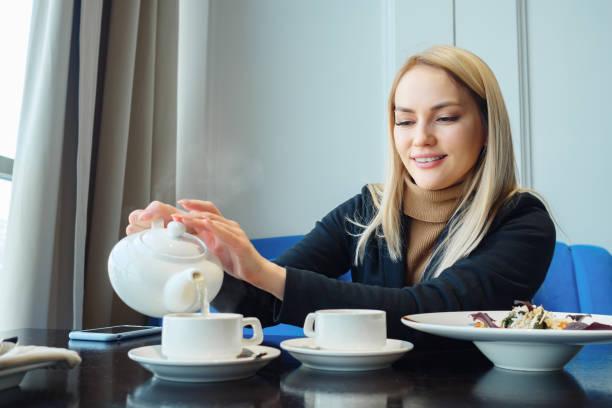 Attraktive Frau sitzt und gießt tagsüber heißen Tee in eine Tasse in einem trendigen Café – Foto