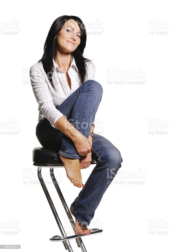 Attractive woman sits on bar chair. Isolated royalty-free stock photo