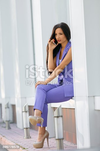 Attractive woman sitting at wall niche talking on phone