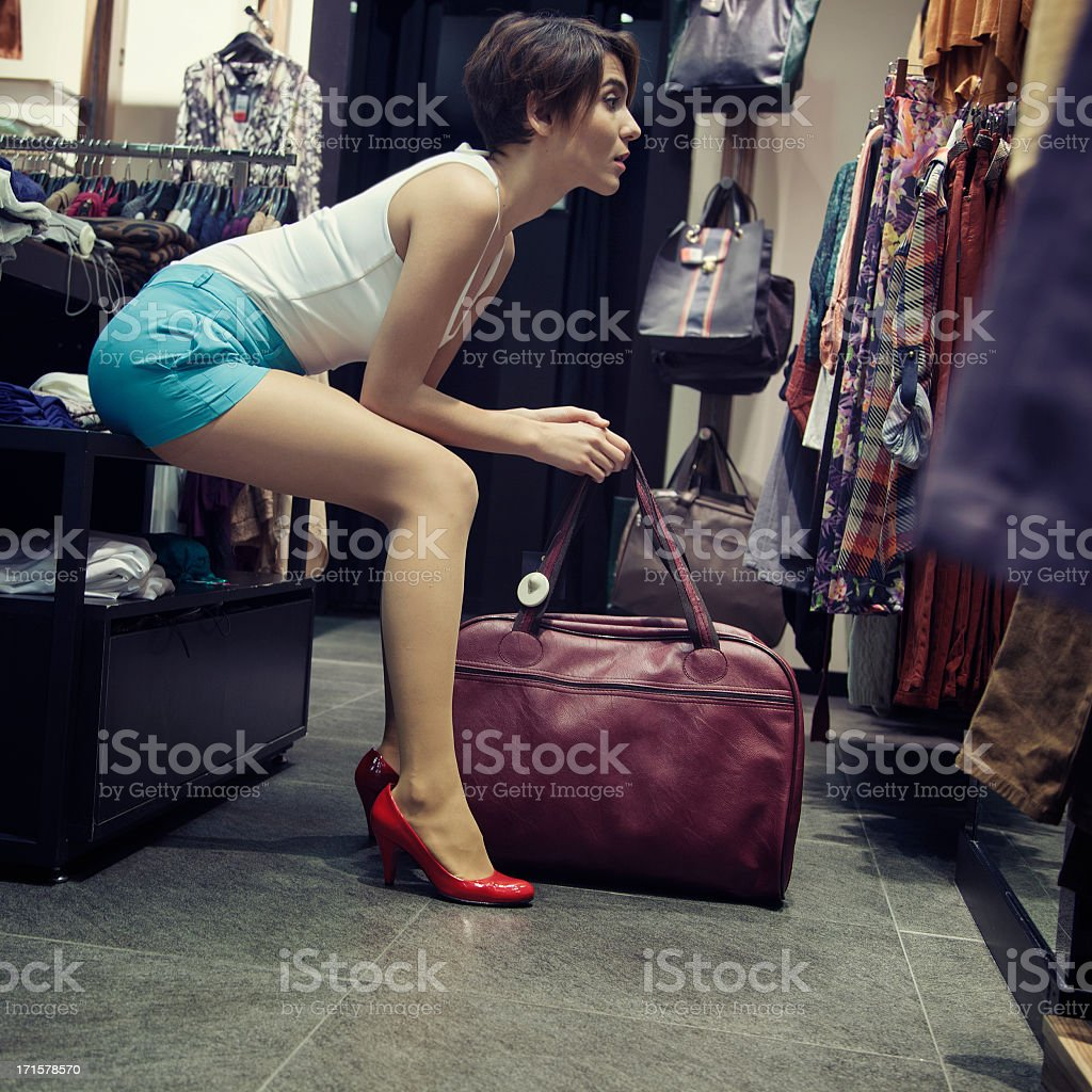 Attractive woman sitting clothes rack with her bag royalty-free stock photo