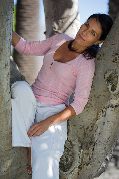 attractive woman sitting in a tree - carolinemaryan stock pictures, royalty-free photos & images