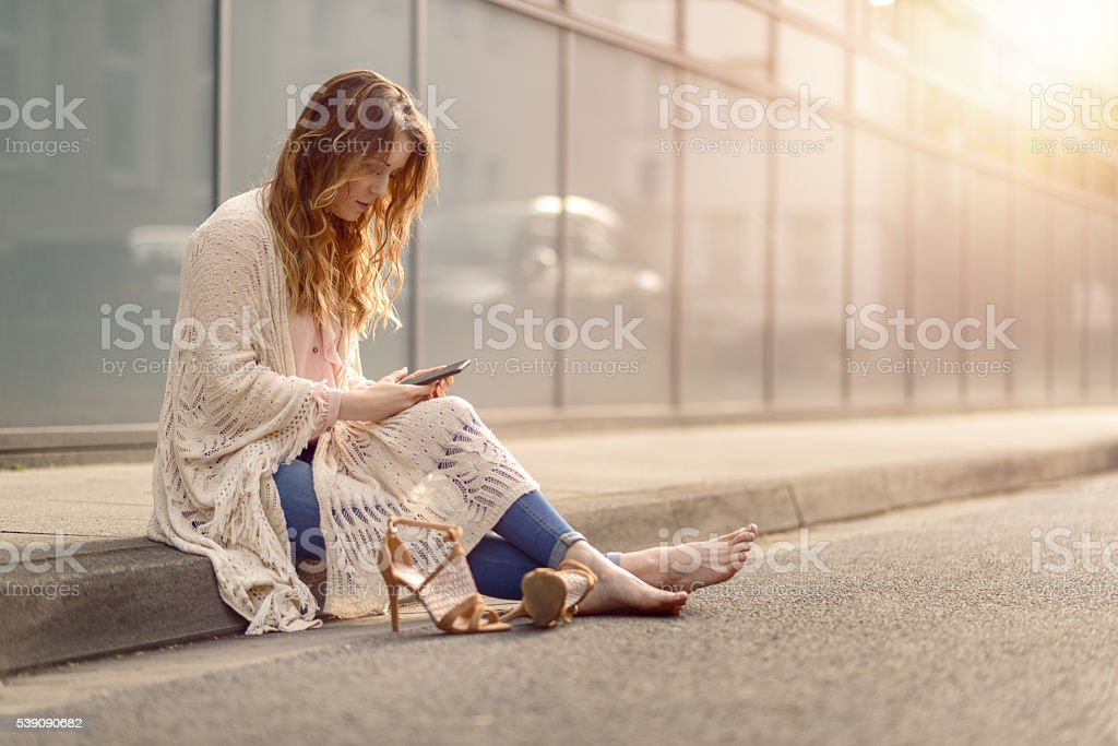 Attractive woman sitting on the kerb of a street stock photo