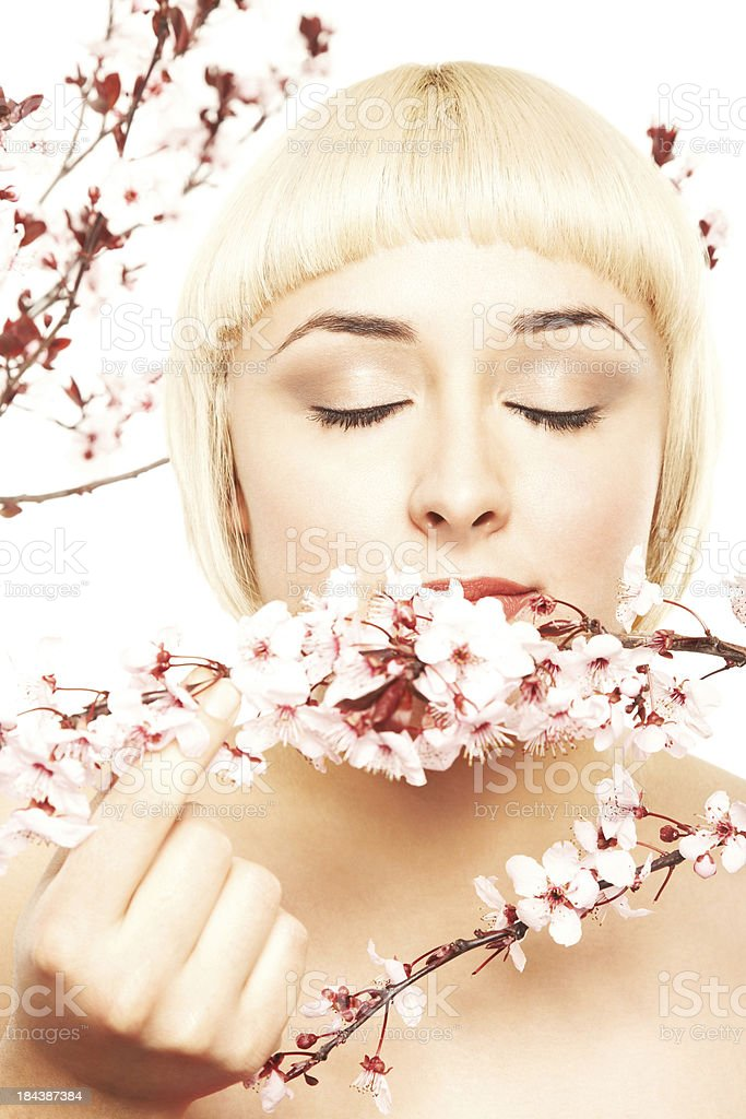 Attractive woman smelling pink cherry blossom flowers royalty-free stock photo