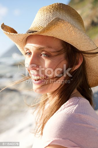 istock Attractive woman smiling with hat at the beach 511540276