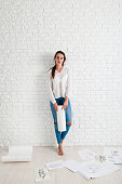 Attractive woman standing in workshop with works, free space. Beautiful barefoot female artist have rest after intensive work, white bricks background. Art, relax, creativity concept
