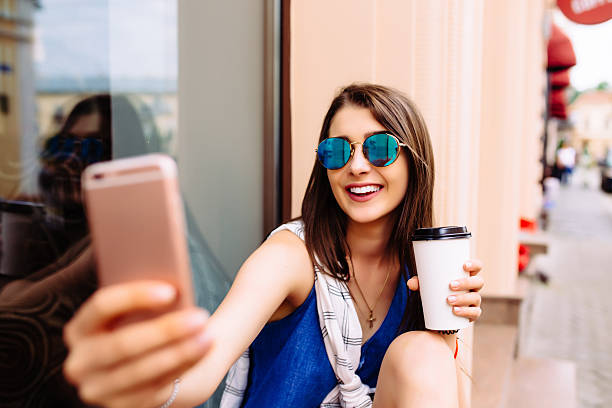 attractive woman taking photo with take-out coffee on her phone - self portrait photography stock pictures, royalty-free photos & images
