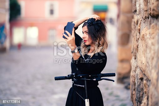 874772840istockphoto Attractive woman taking selfies with phone camera. Portrait of cheerful girl smiling and taking photographs 874772814