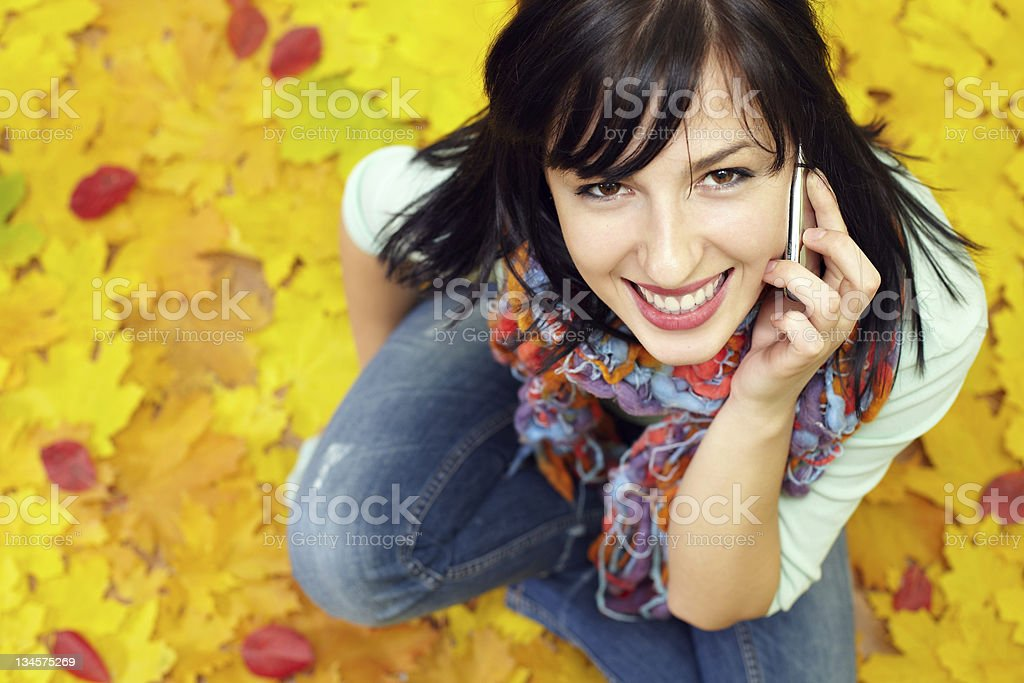 attractive woman talking by cell phone, sitting on fallen leaves royalty-free stock photo