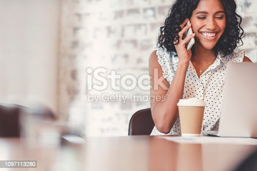 Attractive woman talking on a mobile phone with laptop computer. She is a casually African American woman dressed with curly hair. She looks relaxed and happy with a cup of coffee and she is probably surfing the internet. She could be a business woman working at home or in an office. Background is bricks with copy space.