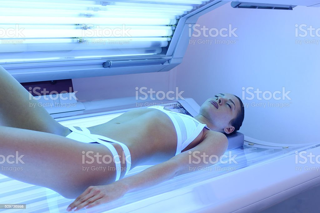 Attractive woman tanning at solarium stock photo