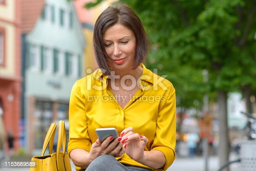 Attractive woman in colorful yellow shirt sitting typing a message on her mobile phone on a bench in an urban street with a happy smile
